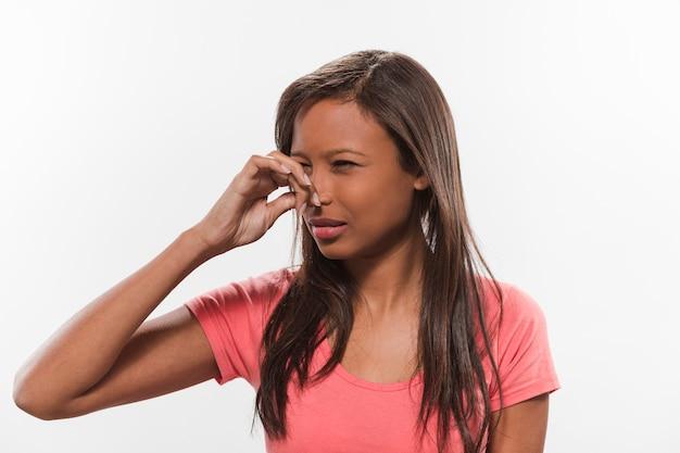 Jolie fille africaine couvrant son nez en raison de la mauvaise odeur Photo gratuit