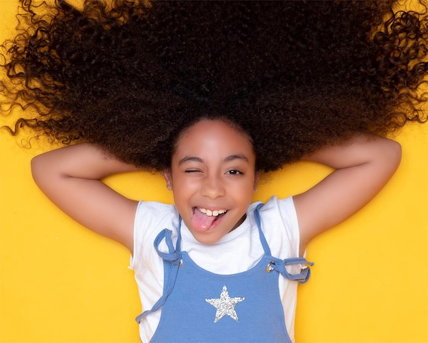 Jolie Fille Afro-américaine Aux Cheveux Bouclés Sourit Et Tire La Langue Photo Premium