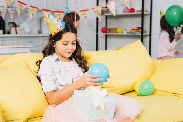Jolie fille d'anniversaire assise sur le canapé tenant un ballon dans la main en regardant une boîte cadeau Photo gratuit
