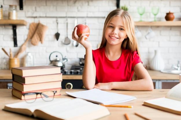 Jolie fille avec apple étudie à la maison Photo gratuit
