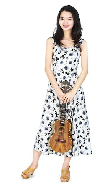 Jolie fille asiatique jouant du ukulélé Photo Premium