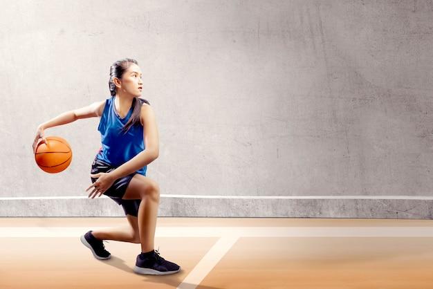 Jolie fille asiatique en uniforme de sport bleu sur pivot de basket bouge sur le terrain de basket Photo Premium