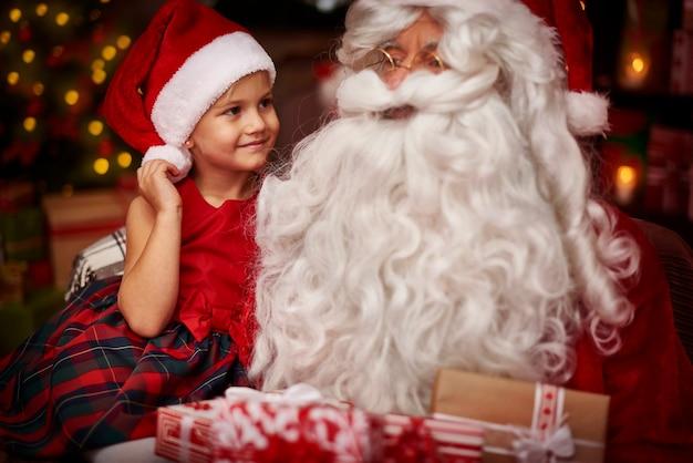 Jolie Fille Assise Sur Les Genoux Du Père Noël Photo gratuit