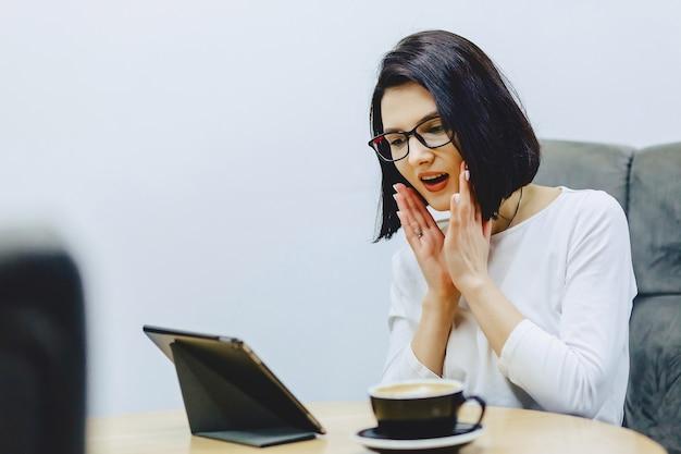 Jolie fille au café boit du café et fonctionne Photo Premium