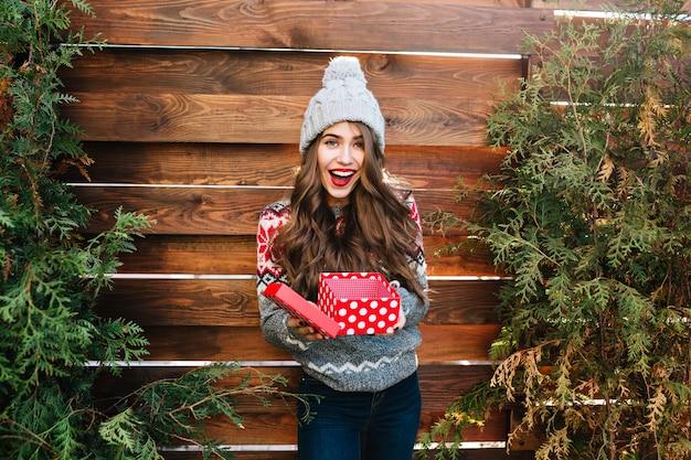 Jolie Fille Aux Cheveux Longs Avec Boîte De Noël Sur Bois. Elle Porte Des Vêtements D'hiver Chauds, Un Bonnet Tricoté, Souriant Heureux. Photo gratuit