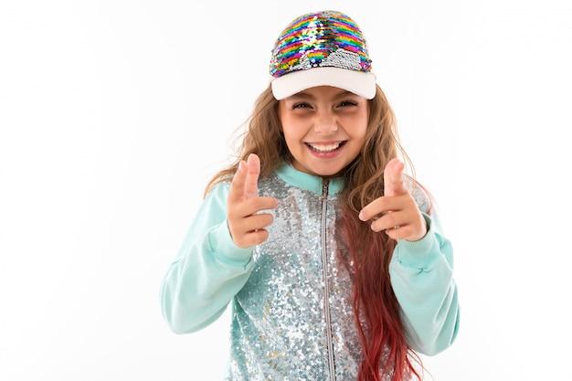 Jolie Fille Aux Cheveux Longs Avec Un Costume De Sport Décontracté Et Une Casquette De Baseball Montre Une Classe à La Caméra Sur Un Fond Blanc Photo Premium
