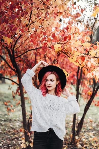 Jolie fille aux cheveux rouges et chapeau marchant dans le parc, temps d'automne. Photo Premium