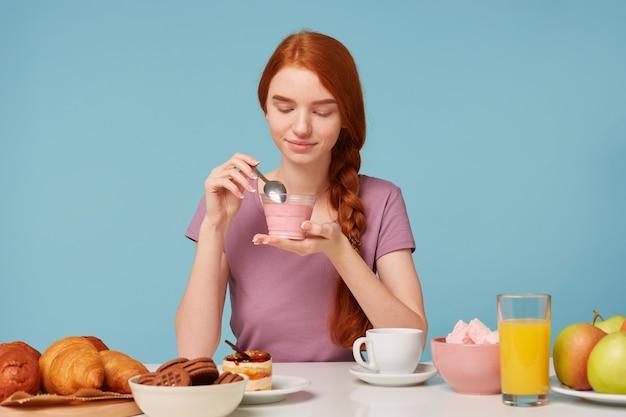 Une Jolie Fille Aux Cheveux Roux Avec Une Tresse Est Assise à Une Table, Déjeune, Tient Dans Ses Mains Un Yaourt Aux Cerises Photo gratuit