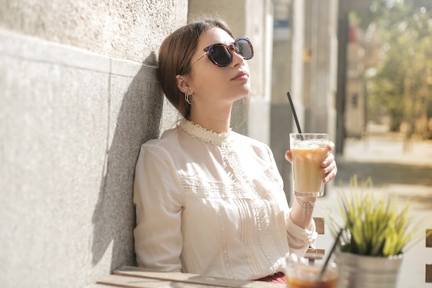 Jolie fille ayant un café glacé Photo Premium