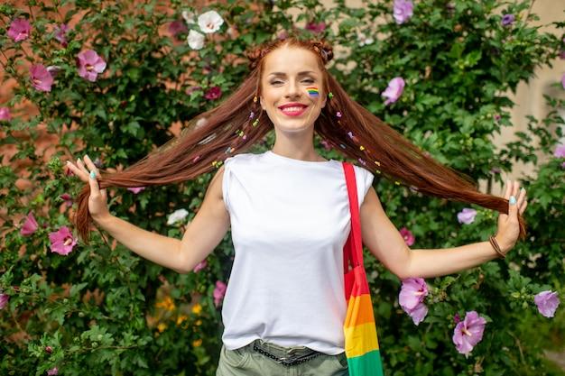 Jolie Fille Bisexuelle Avec Drapeau Lgbt Sur Son Visage Posant Dans Des Buissons Avec Des Fleurs épanouies. Photo Premium