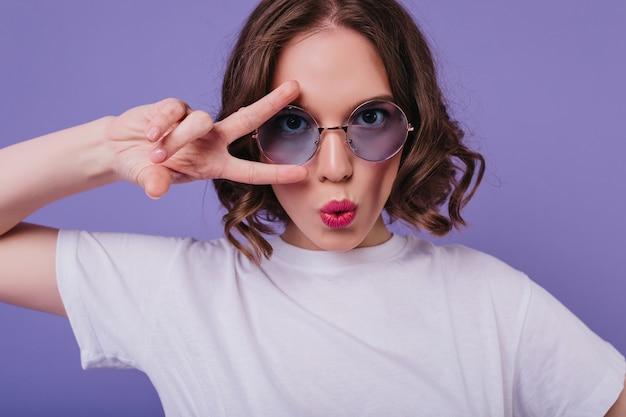 Jolie Fille Blanche Porte Un T-shirt Posant Avec Signe De Paix En Studio. Blithesome Modèle Féminin Brune à Lunettes De Soleil S'amusant Sur Le Mur Violet. Photo gratuit