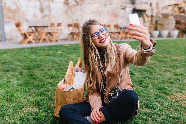 Jolie Fille Blonde Dans Des Verres Faisant Selfie Avec La Main Assise Sur L'herbe Verte Dans Le Parc. Charmante Jeune Femme Se Reposer Après Le Shopping Et Faire Une Photo Pour Le Profil Instagram Avec Les Jambes Croisées Photo gratuit