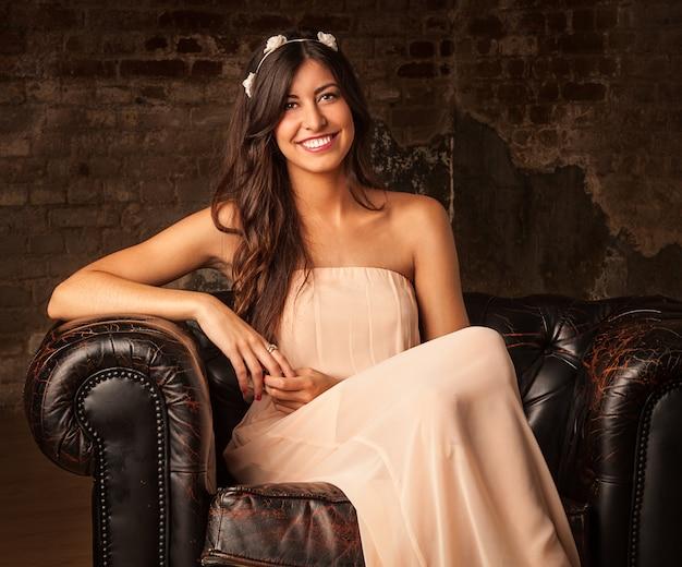 Jolie fille brune assise sur un canapé en cuir avec fond de mur de brique Photo Premium