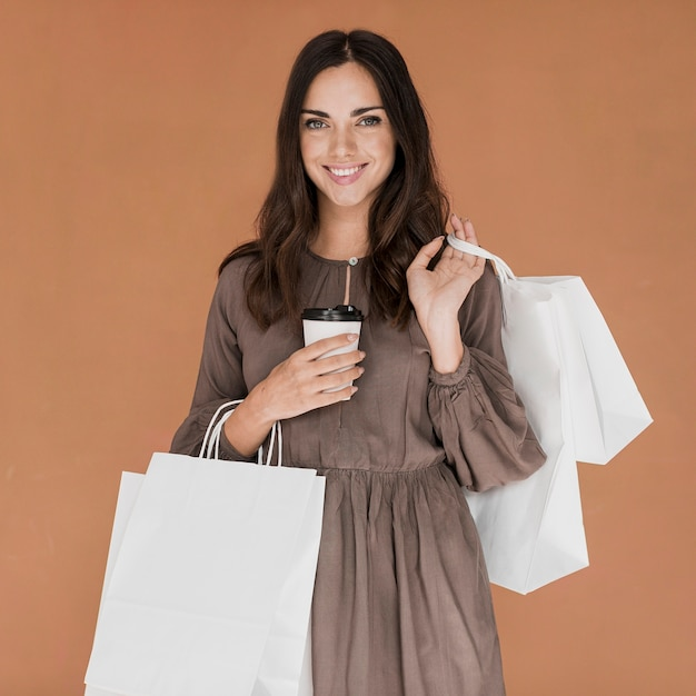 Jolie fille avec café et nombreux filets de magasins souriant à la caméra Photo gratuit
