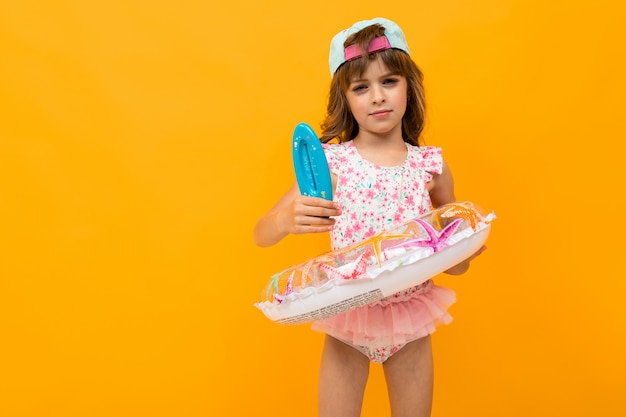Jolie Fille Avec Une Casquette De Baseball En Maillot De Bain Avec Un Cercle De Natation Détient Un Thermomètre Pour L'eau Sur Jaune Photo Premium