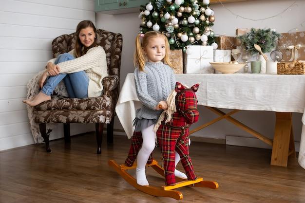 Jolie Fille Sur Cheval Jouet Dans La Cuisine De Noël à La Maison. Photo Premium