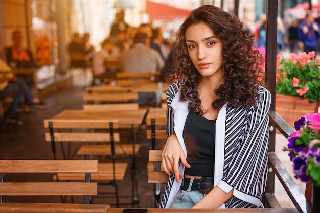 Jolie fille avec les cheveux ondulés, portrait d'une fille dans un café. Photo Premium