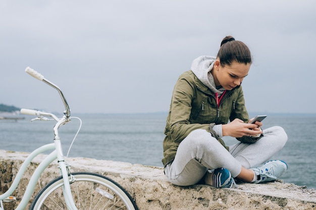 Jolie fille dans une veste verte bénéficie d'un téléphone mobile Photo Premium
