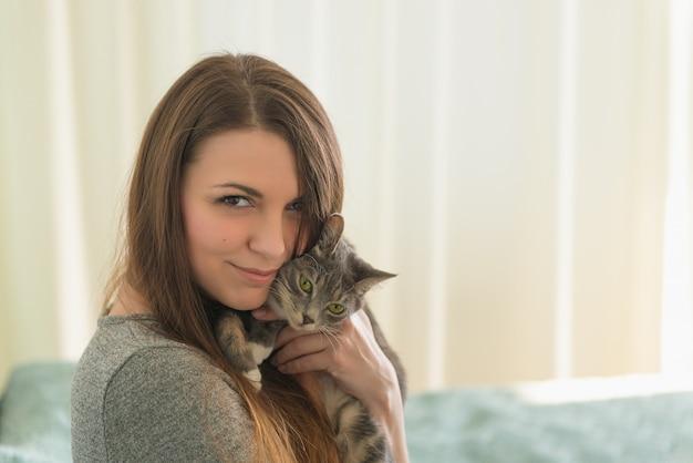 Jolie fille embrasse le petit chat gris dans la chambre le matin. thème des animaux domestiques. Photo Premium