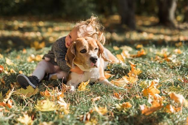Jolie fille étreignant son animal de compagnie dans l'herbe Photo gratuit