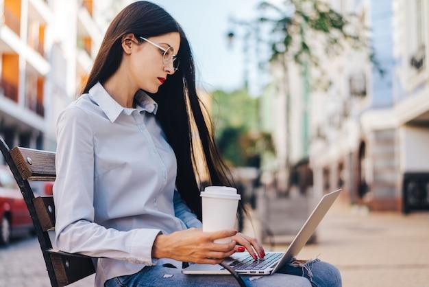 Jolie Fille étudiante Habillée Avec Désinvolture Assise à L'extérieur Sur Une Banque Appréciant Son Café Et Travaillant à L'aide D'un Ordinateur Portable Photo Premium