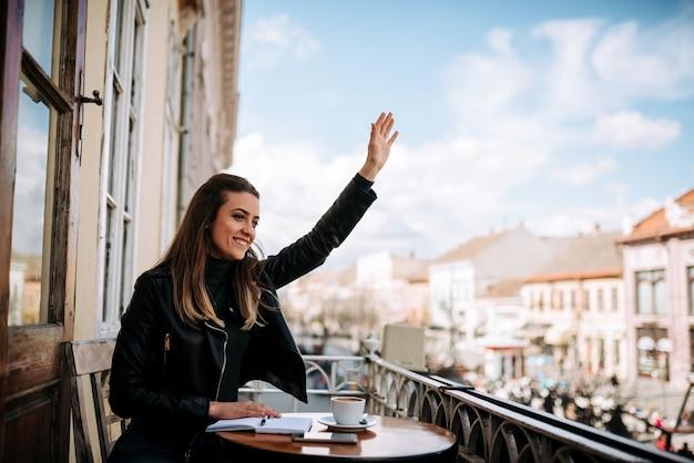 Jolie fille faisant signe à un ami depuis un balcon. Photo Premium