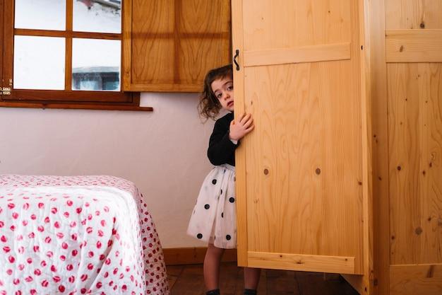 Jolie fille furtivement de placard en bois Photo gratuit