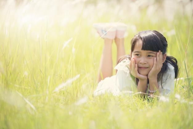 Jolie fille heureuse couché sur l'herbe. Photo Premium