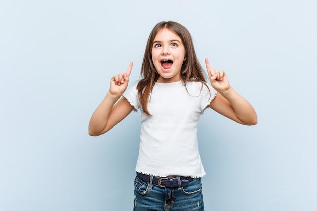 Une jolie fille indique avec ses deux doigts antérieurs un blanc. Photo Premium