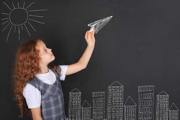 Jolie fille jetant un avion en papier, dessin sur tableau noir Photo Premium