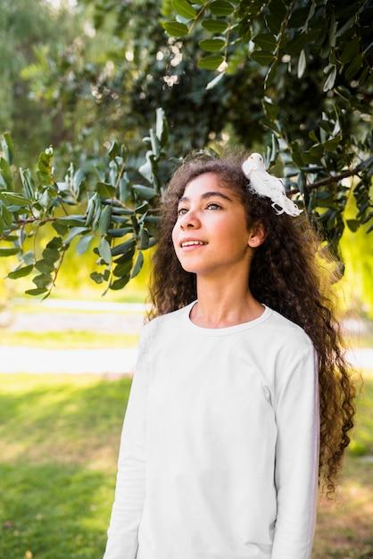 Jolie fille jouant avec ses cheveux bouclés, debout devant l'arbre Photo gratuit