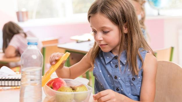 Jolie Fille Mangeant Au Concept De L'école Photo gratuit