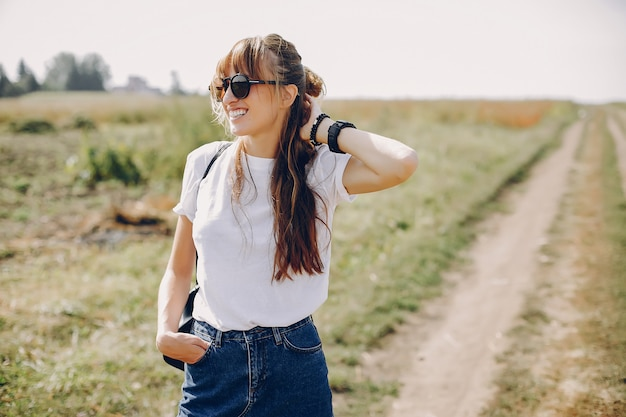 Jolie fille marchant dans un champ d'été Photo gratuit