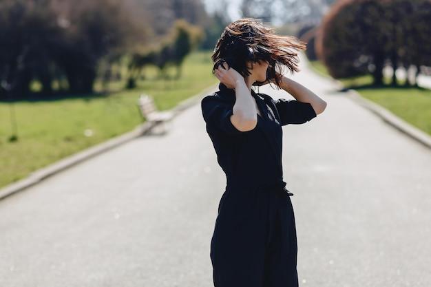 Jolie fille marchant sur la route du parc en journée ensoleillée Photo Premium