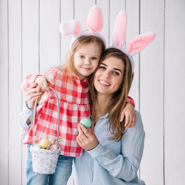 Jolie fille et mère debout avec panier d'oeufs de pâques Photo gratuit