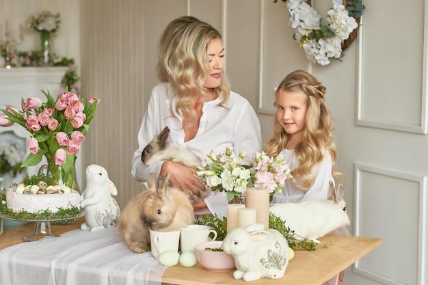 Jolie Fille Et Mère Jouant Avec Des Lapins Photo Premium
