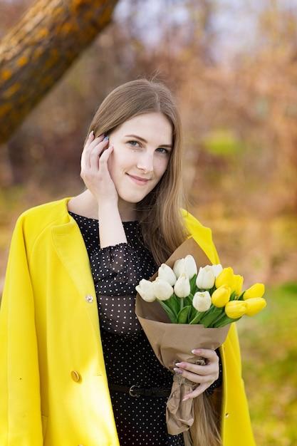 Jolie Fille Mignonne Aux Cheveux Longs Dans Un Manteau Jaune Et Un Bouquet De Fleurs Dans Ses Mains Photo Premium