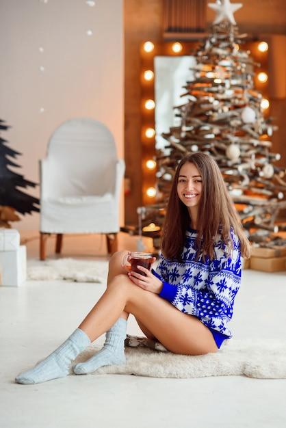 Une jolie fille mignonne dans un pull de vacances tricoté est assis sur un tapis blanc chaud avec une tasse de thé chaud Photo Premium