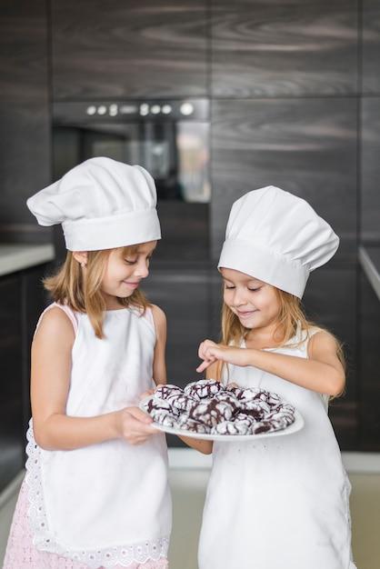 Jolie fille montrant des biscuits cuits au four à sa soeur Photo gratuit