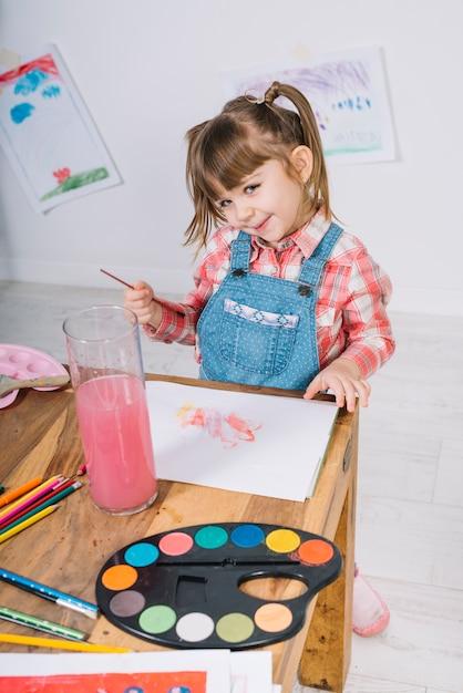 Jolie fille peignant à l'aquarelle sur papier Photo gratuit