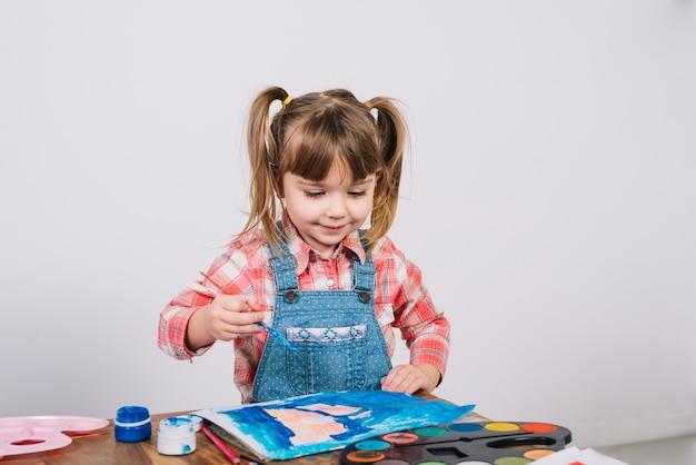 Jolie fille peignant à la gouache sur une table en bois Photo gratuit