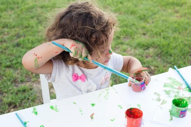Jolie fille peinture au pinceau dans le parc Photo gratuit