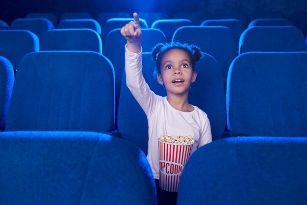 Jolie Fille Poinitant Avec Le Doigt à L'écran Au Cinéma. Photo gratuit