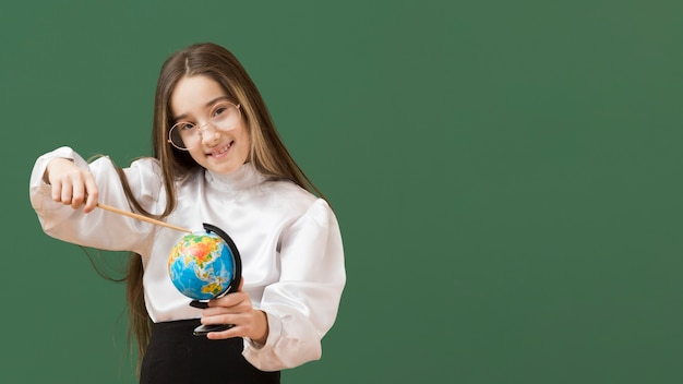 Jolie Fille Pointant Sur Globe Photo gratuit