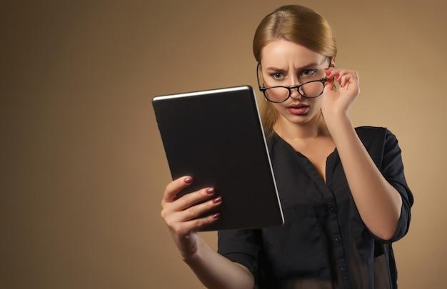 Jolie Fille Prenant Des Lunettes Et Regardant La Tablette Avec Le Visage Confus Photo Premium
