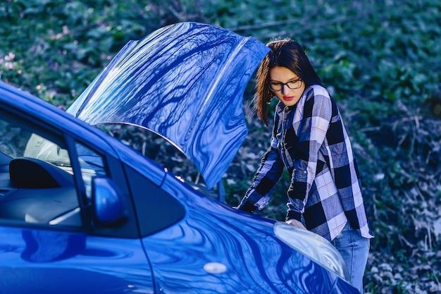 Jolie fille répare la voiture sur la route Photo Premium