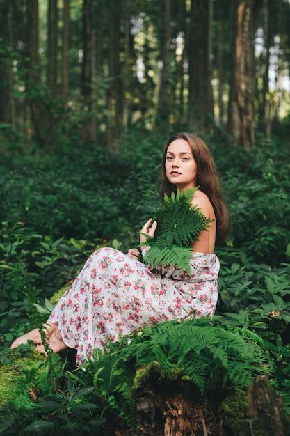 Une Jolie Fille En Robe à Fleurs Est Assise Avec Un Bouquet De Fougère Dans La Forêt. Photo Premium