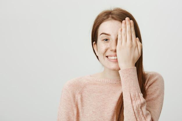 Jolie Fille Rousse Souriante Vérifiant Sa Vue Au Magasin D'opticien, Couvrir La Moitié Du Visage Avec La Main Photo gratuit