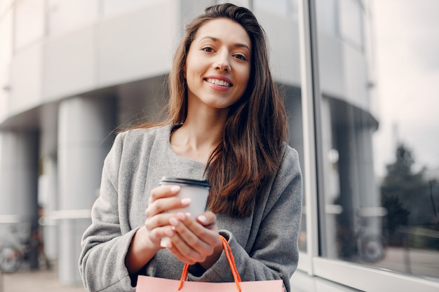 Jolie fille avec un sac dans une ville Photo gratuit