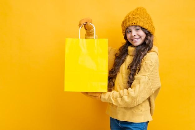 Jolie fille avec un sac shopping jaune Photo gratuit